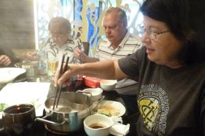 Struggling to gracefully master the Chongqing hot pot.